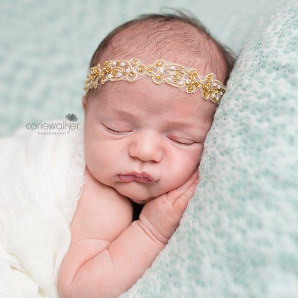 beautiful newborn girl with gold headband